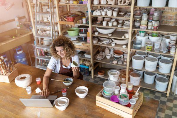 Female potter using laptop in art studio