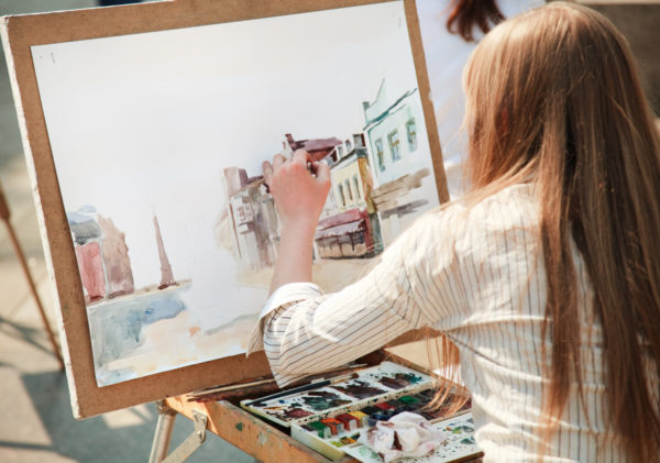 Young woman working on a watercolour painting outdoors