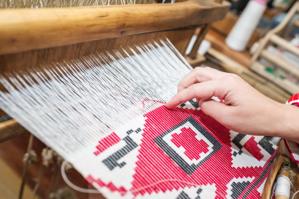 Close-up of tapestry loom with a hand weaving a pattern