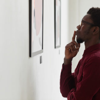 Side view portrait of young Black man looking at paintings and thinking at art gallery