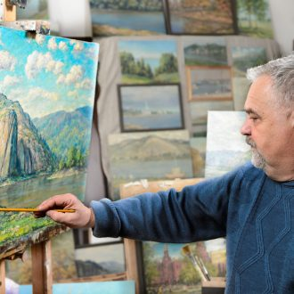 older white artist adding finishes touches to naturescape painting in art studio