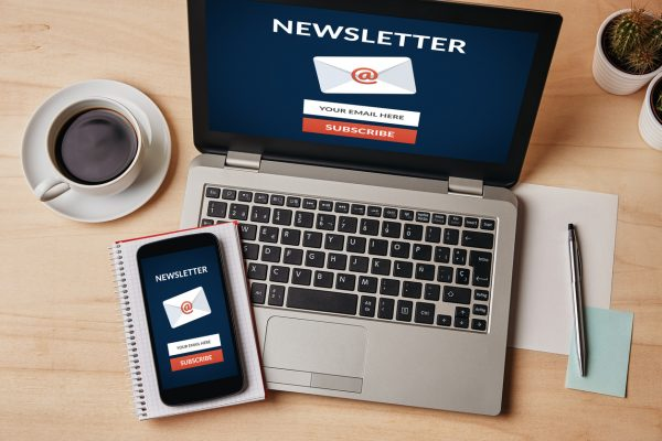 Subscribe newsletter concept on laptop and smartphone screen over wooden table.